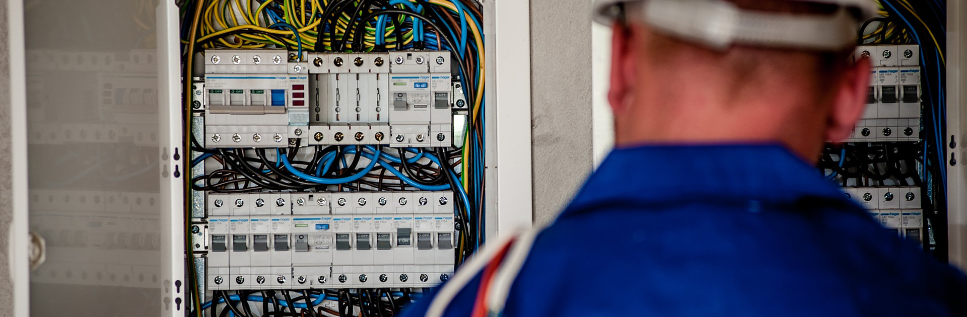 electrician wearing a blue shirt working on an electrical panel